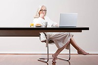 Middle aged woman sitting at table with breakfast and laptop
