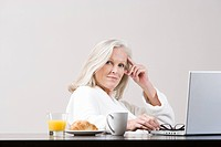Middle aged woman using laptop at breakfast time