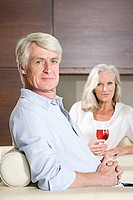 Middle aged couple relaxing with glass of wine