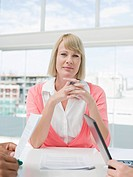 Businesswoman sitting at head of meeting table