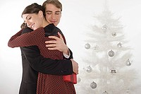 Couple hugging near christmas tree