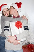 Couple in santa hats kissing
