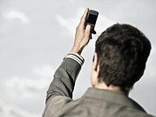 Businessman using cameraphone