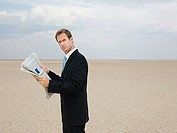Businessman reading a newspaper in the desert