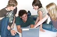 4 young people have fun at a laptop