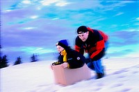 Boy in box being pushed downhill by man