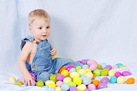 Baby boy playing with color Easter eggs