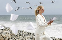Young businesswoman letting paperwork blow away on beach