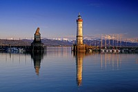 Lighthouse and sculpture of lion at harbour, snow covered Alps in the background, Lindau, Lake Constance, Baden Wurttemberg, Germany