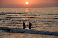 Two people standing in the sea fishing at dusk, Musandam, Oman, Asia