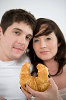 Portrait of young couple holding croissant in bed