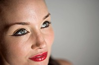 Close_up portrait of young woman with red lipstick and black eyeliner