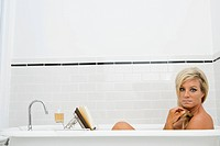 Portrait of mature woman relaxing in bathtub with book and wine
