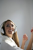 Side view of young happy woman listening to headphones