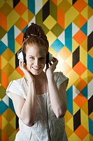 Cheerful young woman listening to music, portrait