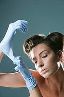 Young woman pulling blue rubber gloves with eyes closed