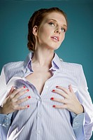 Young woman wearing shirt, grabbing breasts