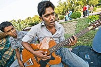 Young man playing the guitar at the National Martyrs Monument park, Dhaka, Bangladesh
