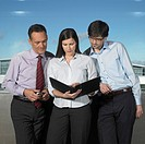 Three Businesspeople looking on book