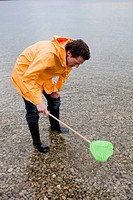 man in raincoat fishing with toy net