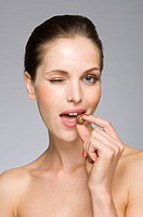 Female beauty model eating chocolate