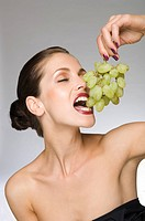 female beauty eating grapes