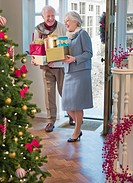 Couple entering house with Christmas gifts
