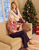 Mother and daughter sitting on sofa near Christmas tree
