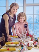Mother and daughter setting table for Christmas dinner
