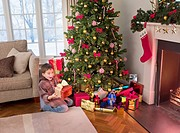 Surprised boy holding gift near Christmas tree