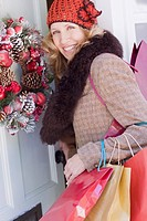 Woman with shopping bags opening door