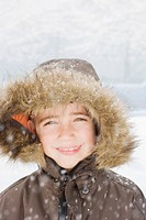 Snow falling on smiling boy