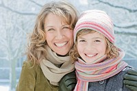 Mother and daughter smiling in snow