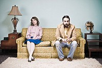 Unhappy couple sitting on living room sofa