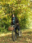 Woman riding bicycle under Autumn trees