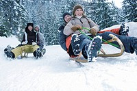 Group of young people with winter clothes having fun riding sled in snowy landscape.