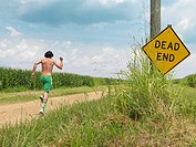 Man in shorts running past Dead End sign