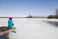 Woman Relaxing on Dock by Frozen Lake