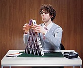 Businessman stacking cards on desk