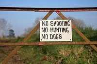 no shooting no hunting no dogs sign on a old rusty metal gate entrance to a field