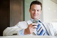 Businessman text messaging on cell phone