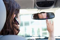 Businesswoman using cell phone in car