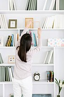 Young woman putting book on bookshelf