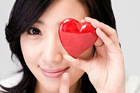 Young woman holding heart shaped ornament, close up