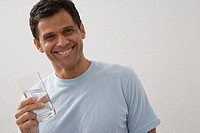 Portrait of a mature man holding a glass of water and smiling