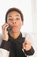 Close_up of a businesswoman talking on a cordless phone and pointing forward