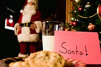 Plate of cookies and milk with Santa Claus in the background