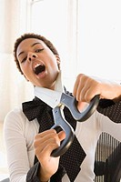 Businesswoman attempting to cut her neck with a pair of oversized scissors