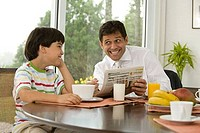 Mature man asking his son for help with puzzle in newspaper at a breakfast table