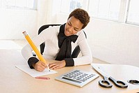 Businesswoman sitting at a desk writing on a sheet of paper with an oversized pencil